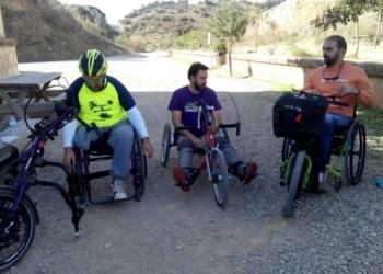 Un grupo de personas con discapacidad, realizando la Vía Verde de la Sierra.