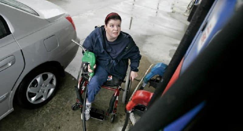 Persona en silla de ruedas echando gasolina
