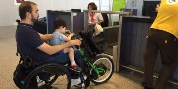 Pasajero en silla de ruedas en facturación aeropuerto