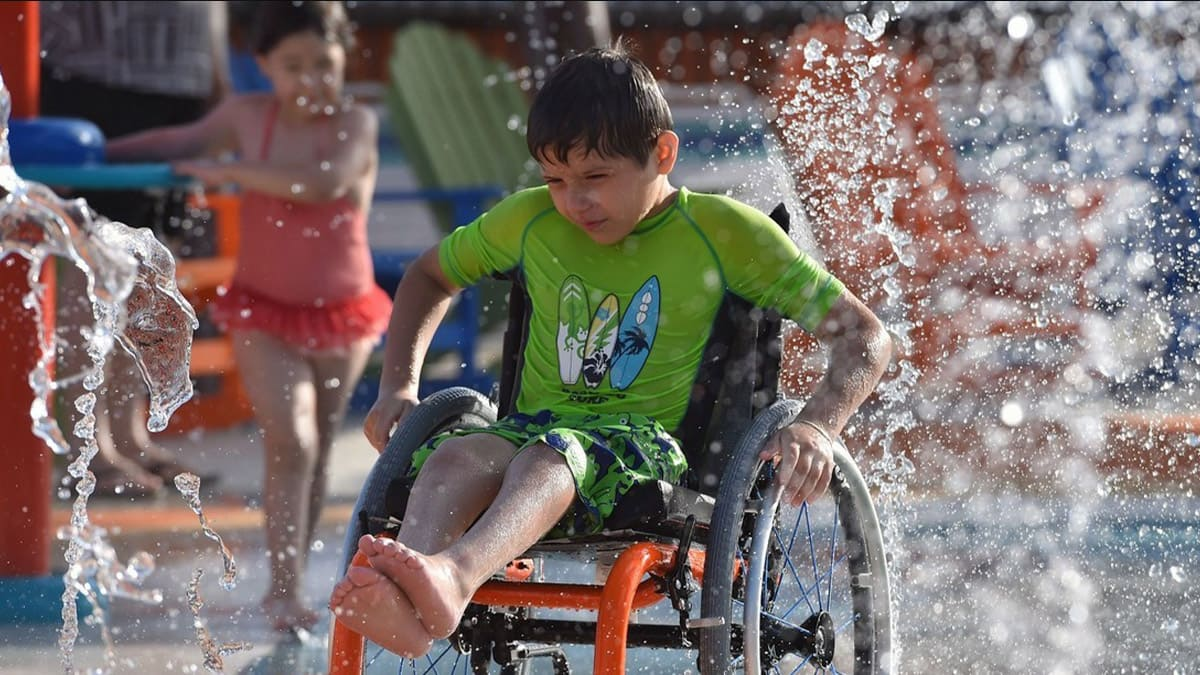 Niño en silla de ruedas en el parque acuático