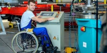 Un trabajador con discapacidad en su puesto de trabajo | Licencia: Bigstock
