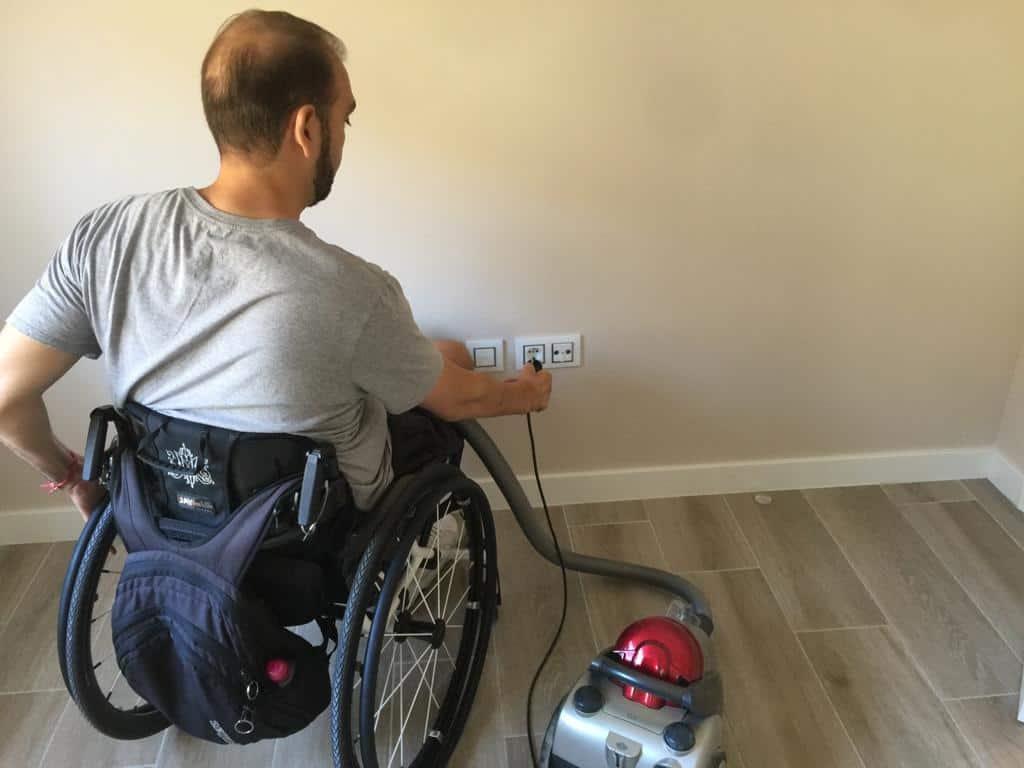 Usuario de silla de ruedas enchufando una aspiradora.