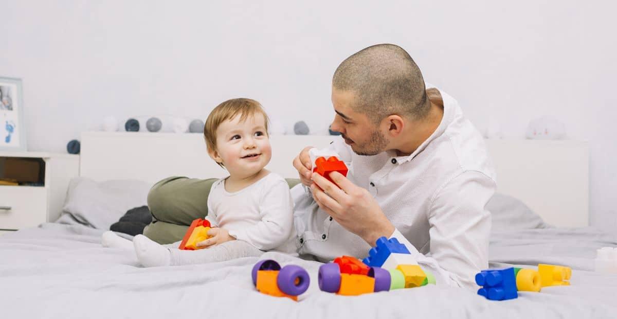 Hombre con un bebé jugando en la cama