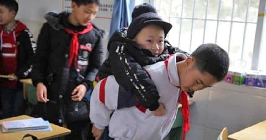 Niño que carga a otro con discapacidad