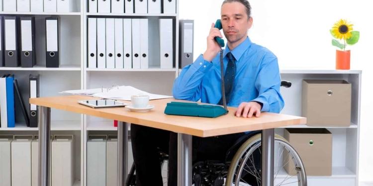 hombre en silla de ruedas junto a mesa escritorio discapacidad empleo publico