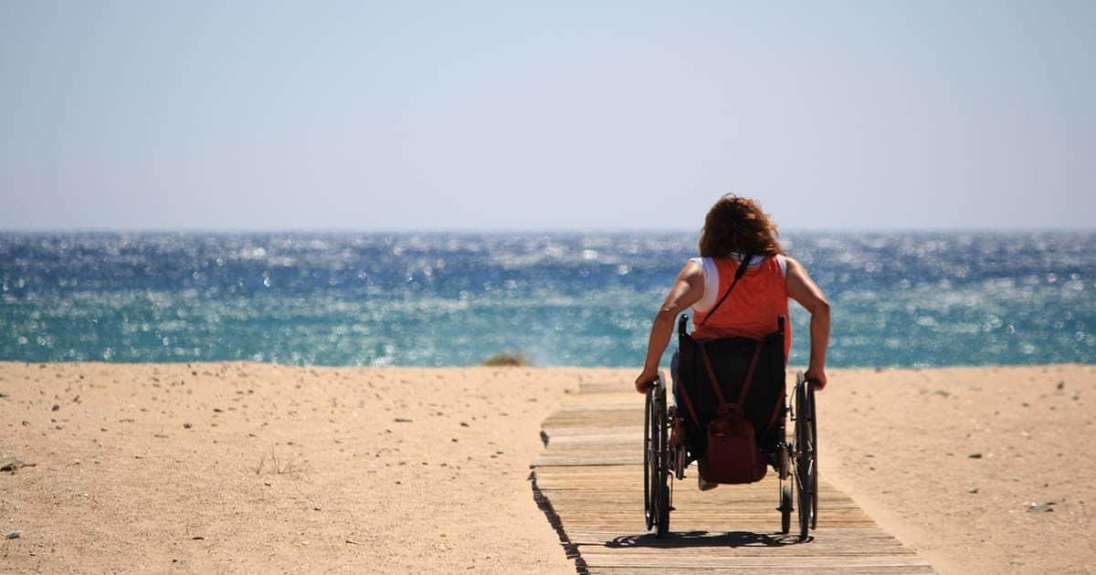 Mujer en silla en la playa, turismo accesible