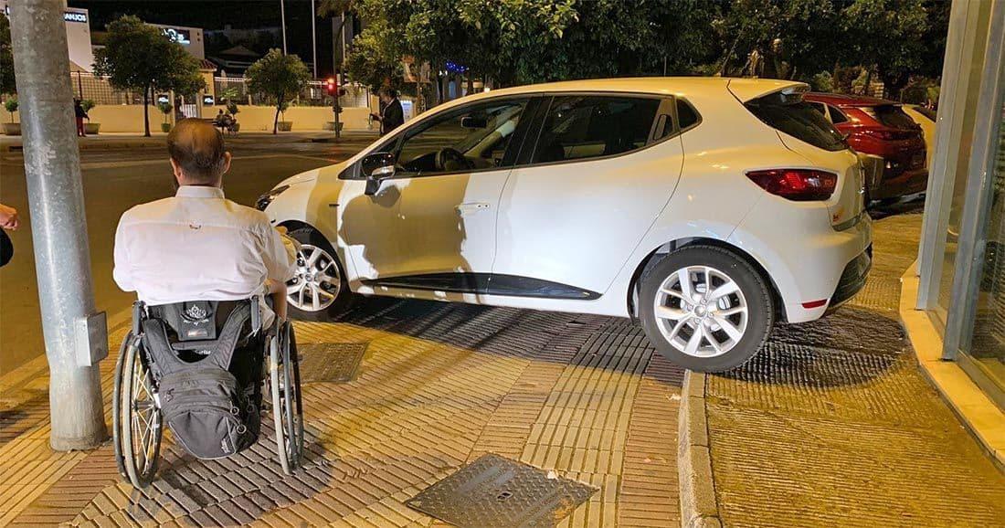 Una Feria con coches en las aceras sin permitir paso de personas en silla de ruedas
