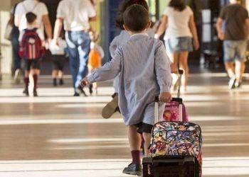 Niño empujando su maleta con ruedas