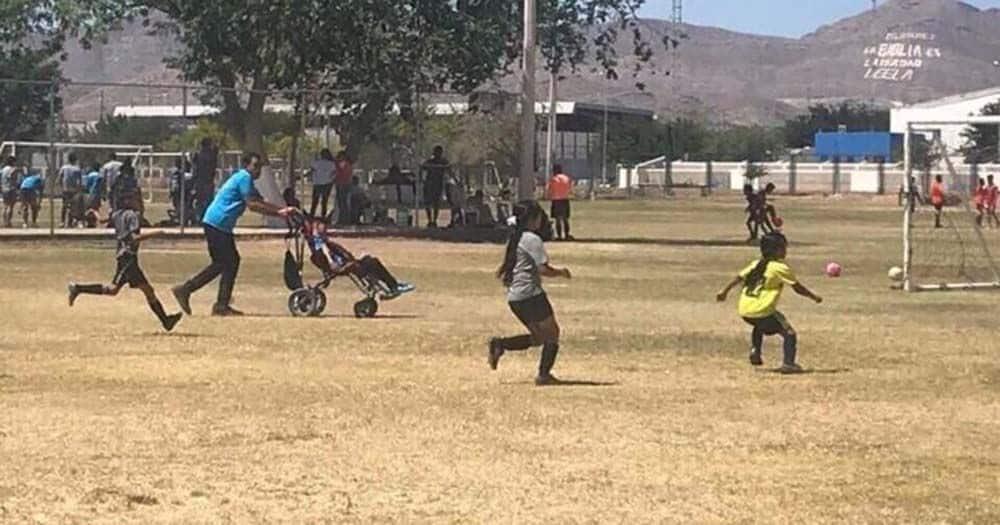Un padre empuja la silla de ruedas de su hijo para que pueda jugar al futbol