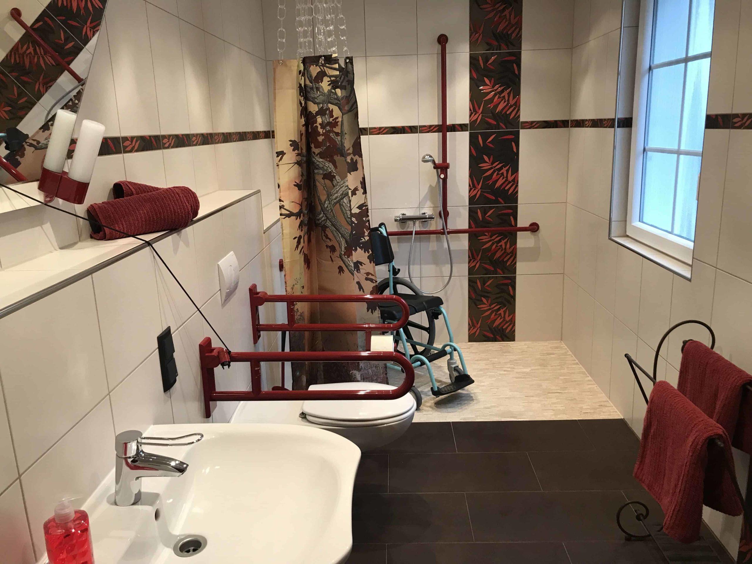 Baño accesible con silla de baño. Tonos blancos y corinto