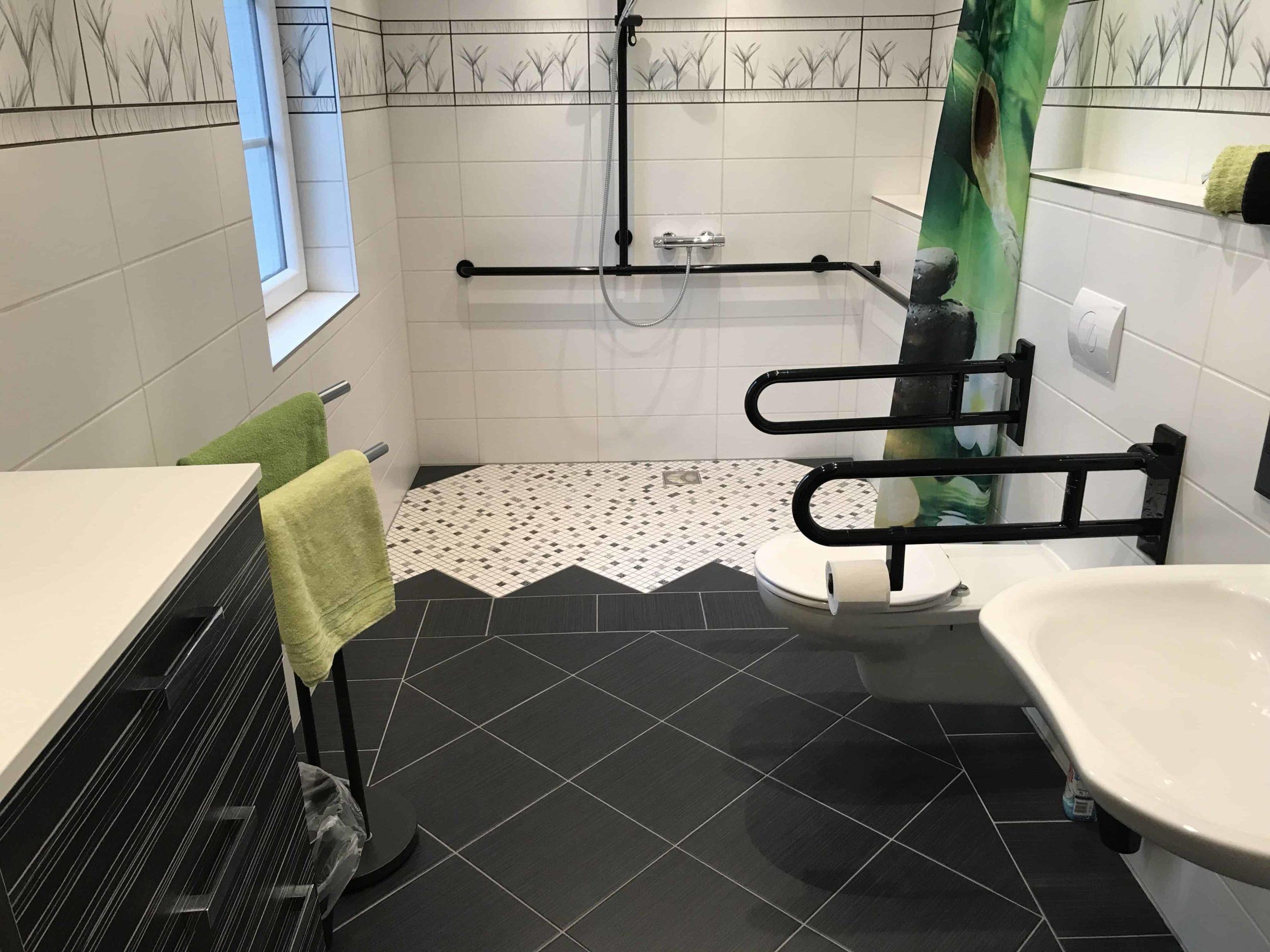 Baño accesible de tonos negro, blanco y verdes. Placa ducha y water con asideros