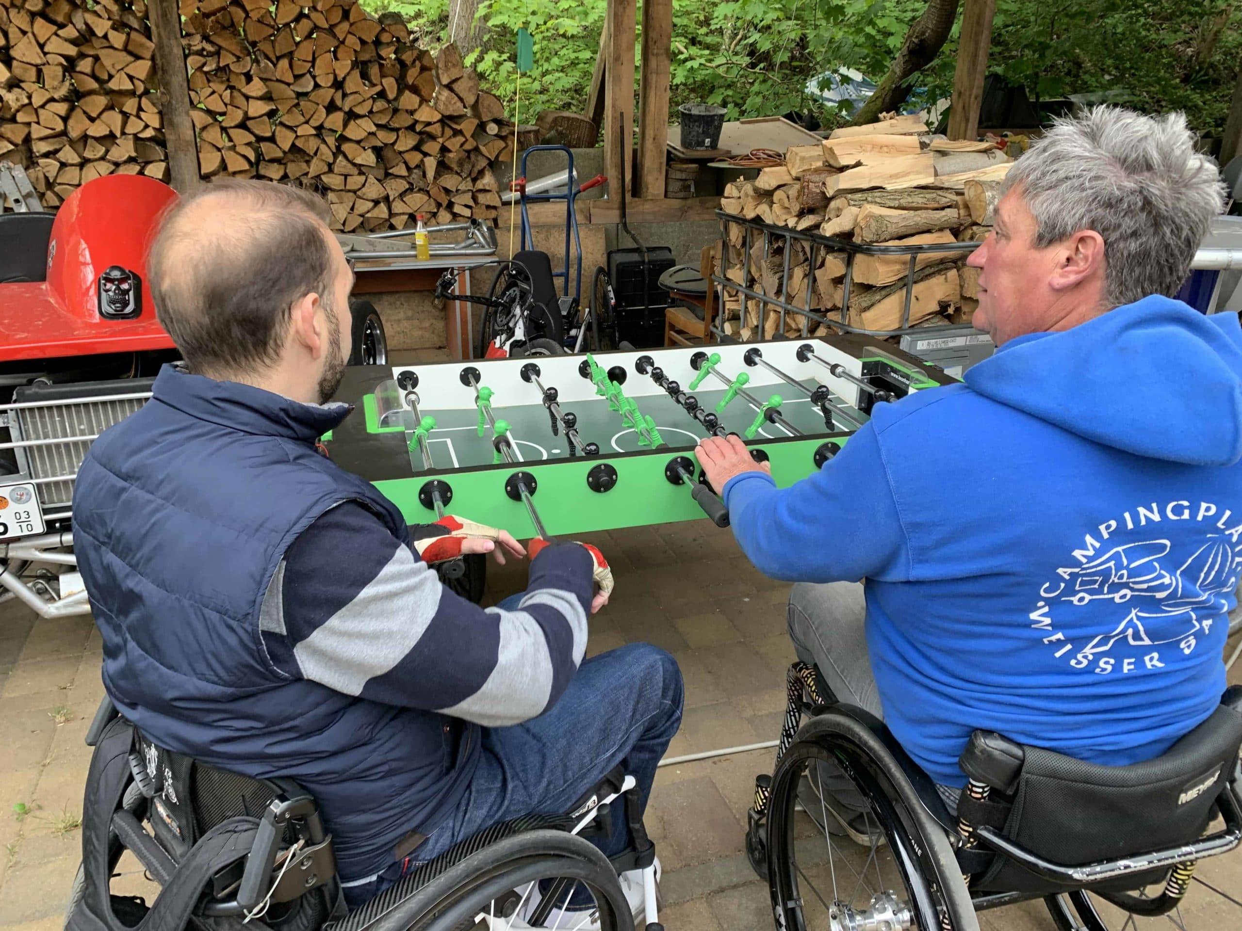 Dos usuarios en silla jugando al futbolín adaptado