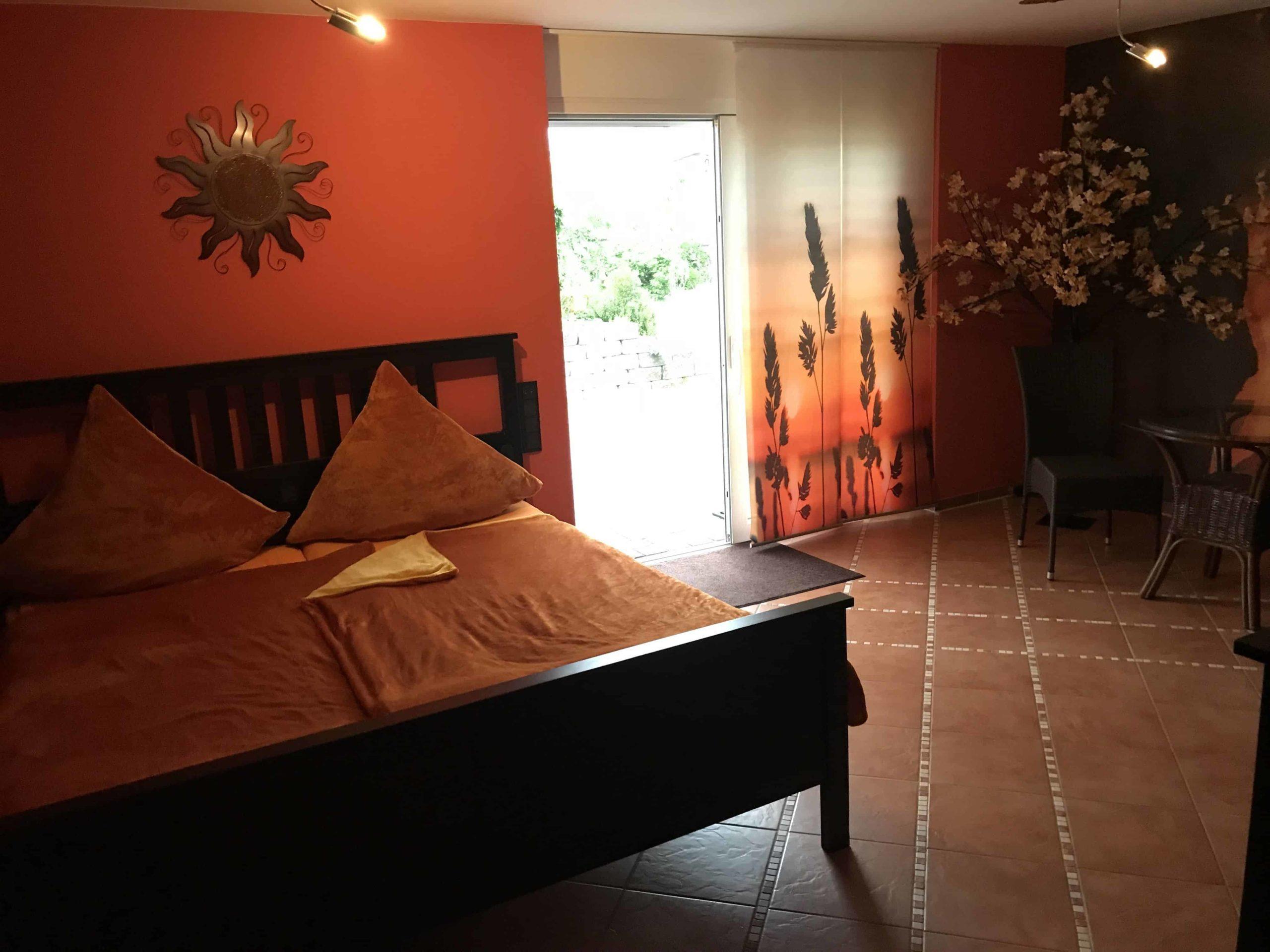 Cama y terraza de la habitación de tonos rojos