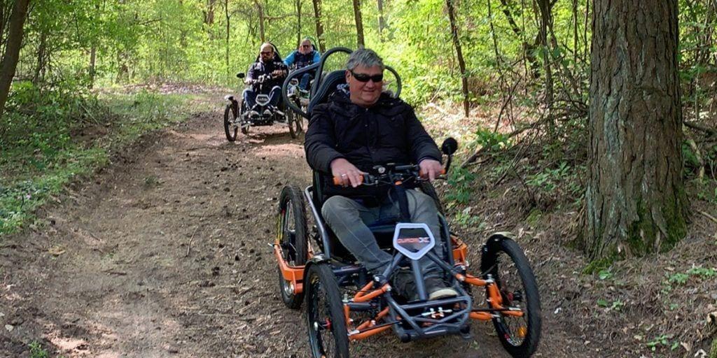 Tres usuarios de silla de ruedas con el Quadrix en los bosques de Brandenburgo