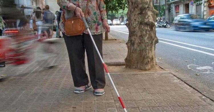 Persona sordociega, con discapacidad visual, con un bastón blanco y rojo