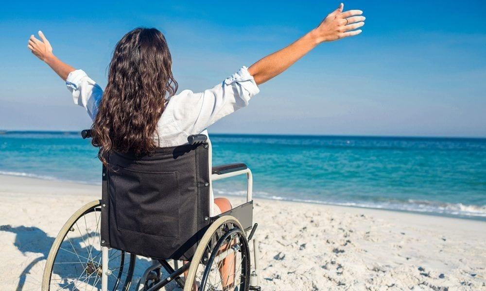 Mujer en silla de ruedas en una playa