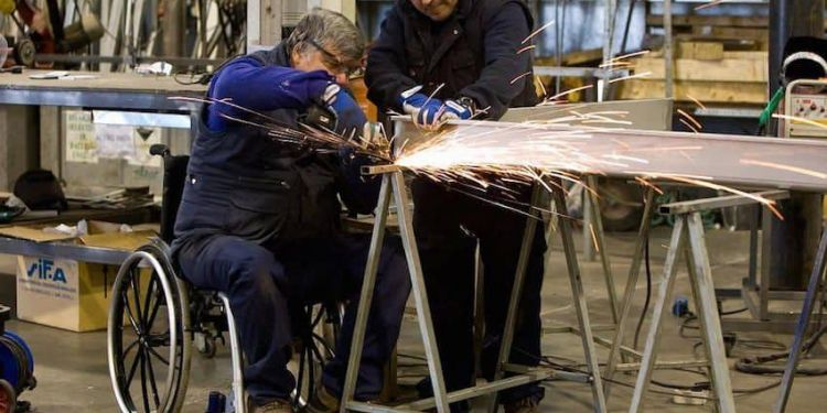 Persona en silla de ruedas soldando en su empleo