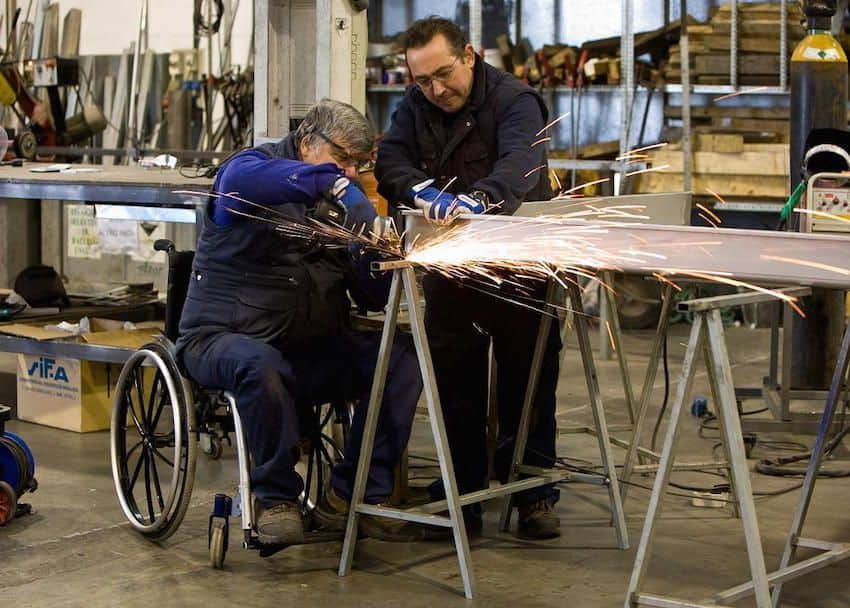 Persona en silla de ruedas soldando