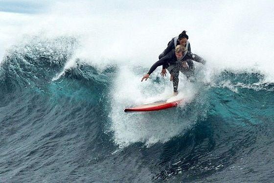 Mujer con paraplejia encima de surfero