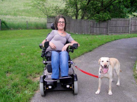 Niña en silla junto a su perro asistente