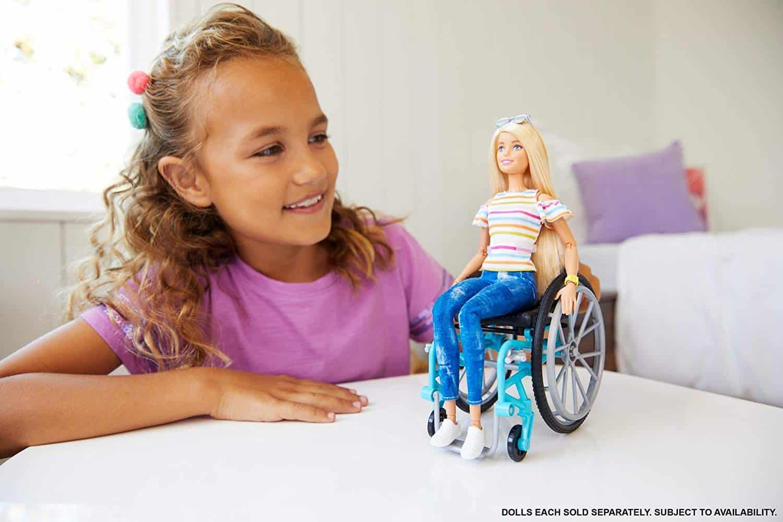 Niña jugando con la barbie silla de ruedas