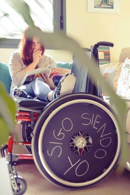 """Una chica sentada en el sofá y sus pies en una silla de ruedas donde pone """"sigo siendo yo"""""""