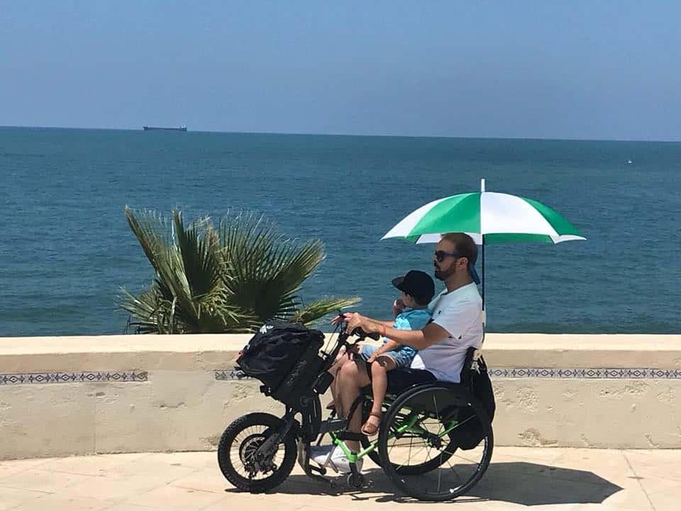 Usuario de silla de ruedas con su Batec e hijo encima