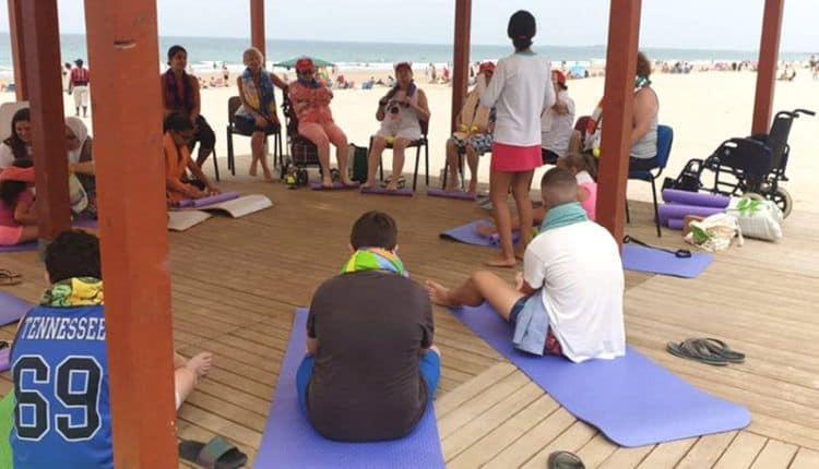 varias personas haciendo yoga en la tarima de la playa