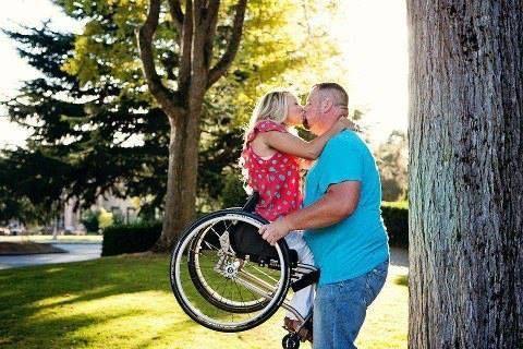 Un hombre levanta a su mujer que va en silla de ruedas para darle un beso