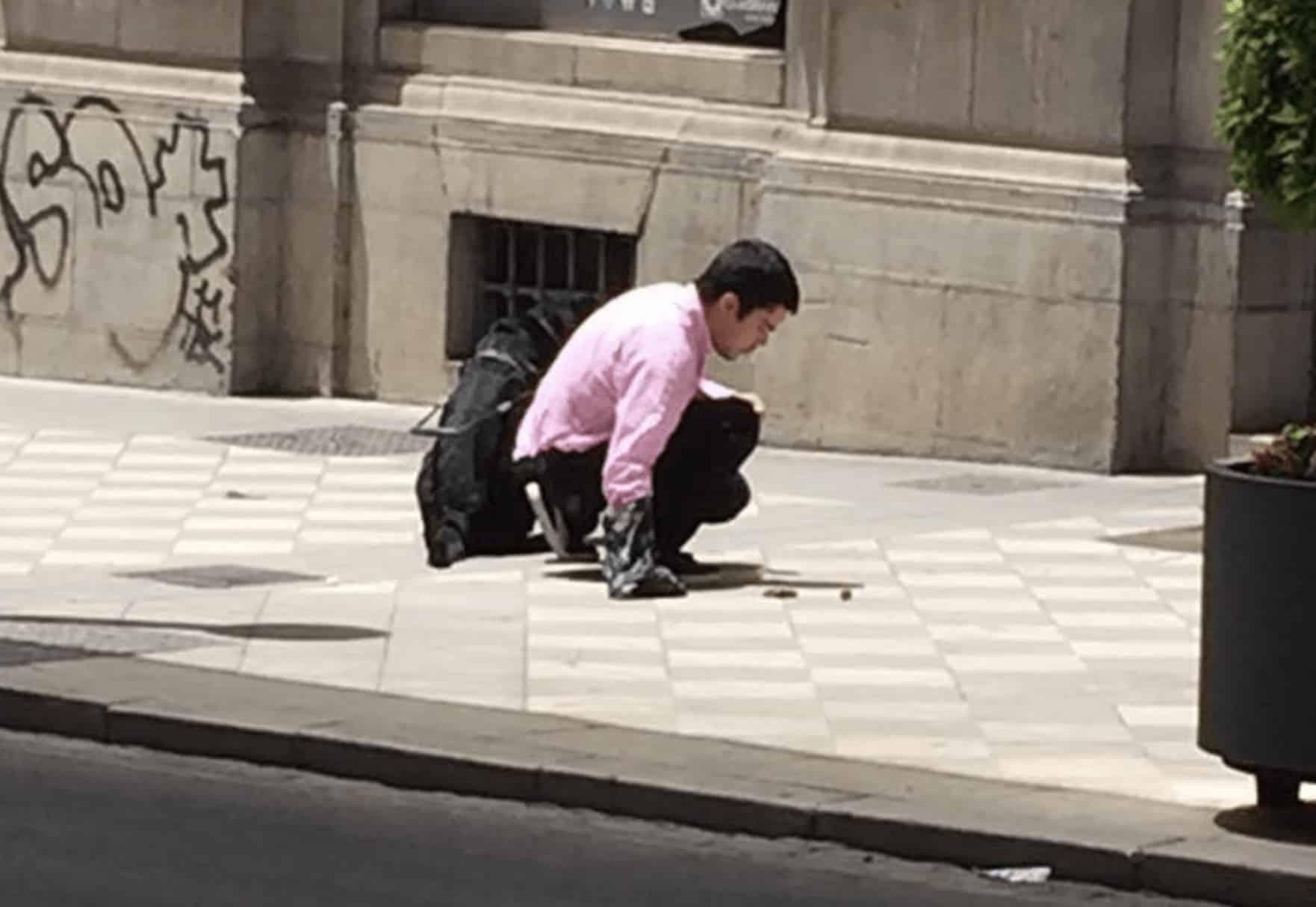 hombre ciego recoge los escrementos de su perro guía