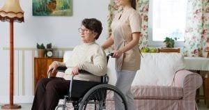 Mujer mayor en silla de ruedas junto a su asistente personal