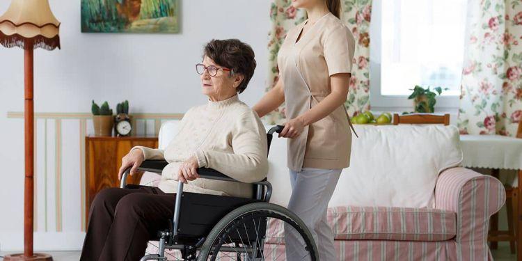 Mujer mayor con discapacidad en silla de ruedas junto a su asistente personal - ley dependencia