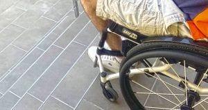 Usuario de silla de ruedas al borde de unas escaleras