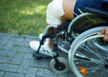 Mano en el aro de la silla de ruedas. Se ve parte del suelo