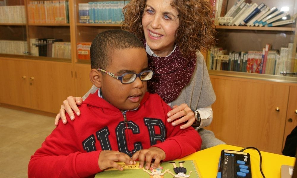 Un niño ciego junto a su maestra