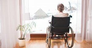 Mujer mayor en silla de ruedas mirando a la ventana. Soledad y dependencia