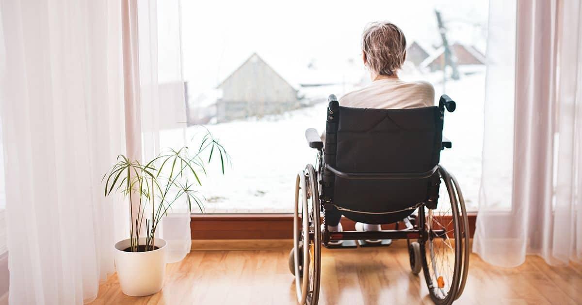 Mujer mayor en silla de ruedas mirando a la ventana. Soledad y dependencia | Persona dependiente servicio de dependencia