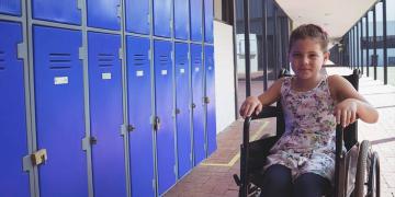 Niña en silla de ruedas junto a taquillas de un centro