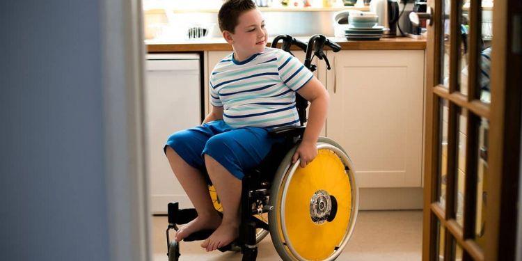 Niño en silla de ruedas en la cocina