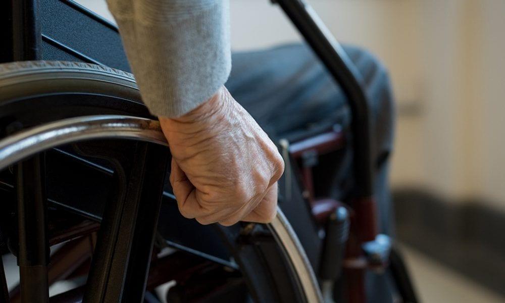 Mano en el aro de una silla de ruedas