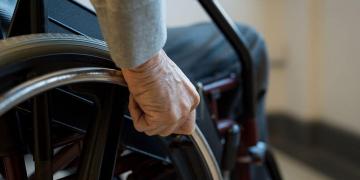 Mano en el aro de una silla de ruedas discapacidad