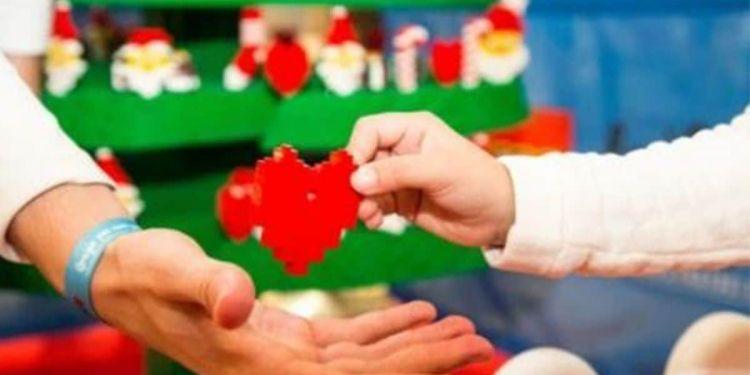 Una niña entrega un adorno navideño hecho con piezas Lego