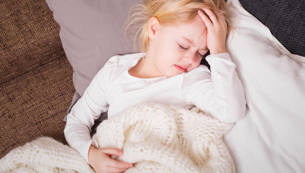 Niña con migraña quejándose del dolor de cabeza