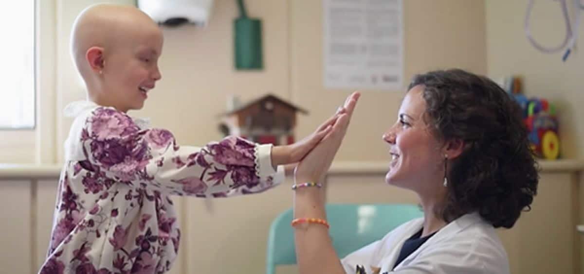 Niña con cáncer junto a una enfermera