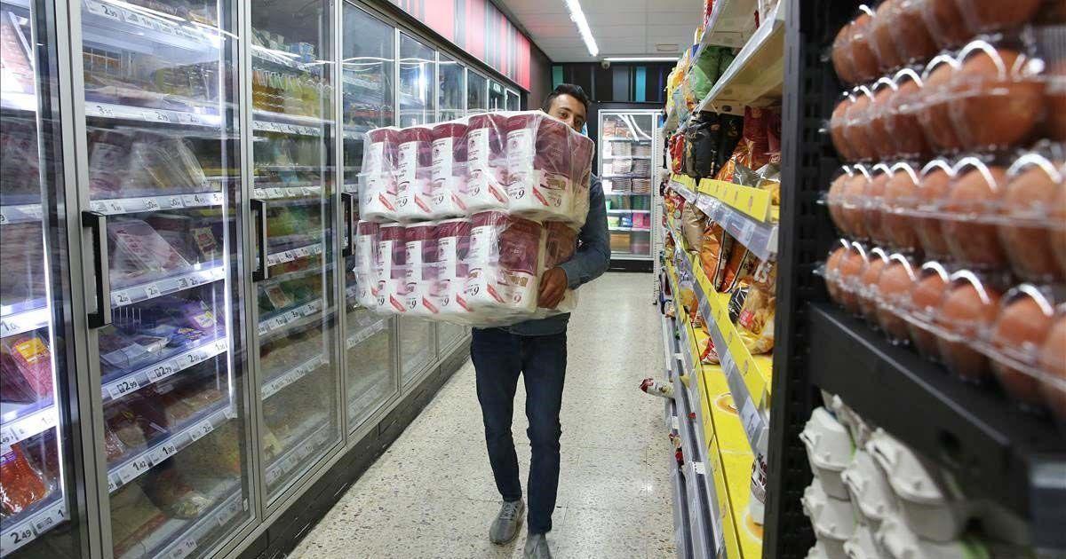 Personal recargando el papel higiénico en un supermercado