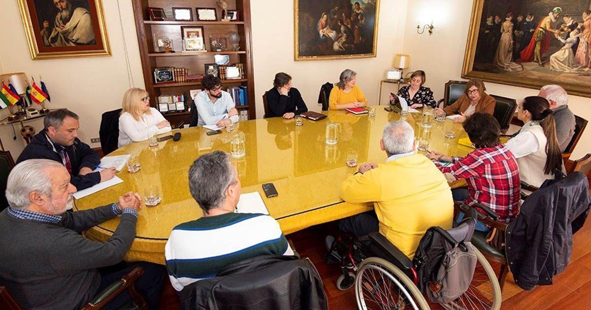 Miembros de la diputación de Cáceres reunidos con personas con discapacidad para cerrar el convenio