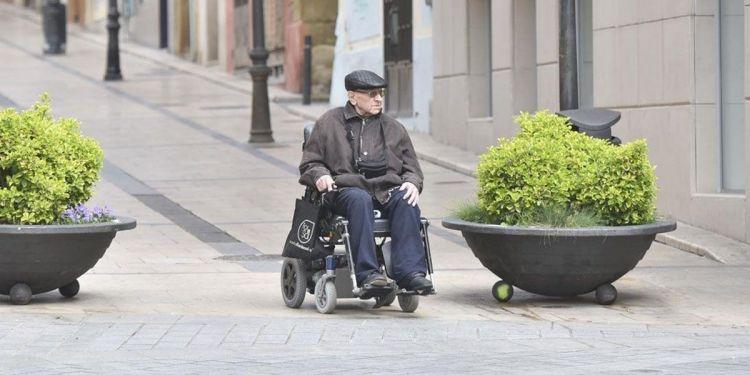 Anciano con discapacidad junto a su silla de ruedas por la calle
