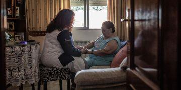 Una cuidadora de la dependencia junto a una persona mayor.