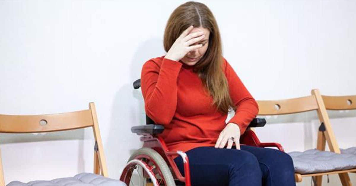 Mujer en silla de ruedas tocándose la cabeza discapacidad