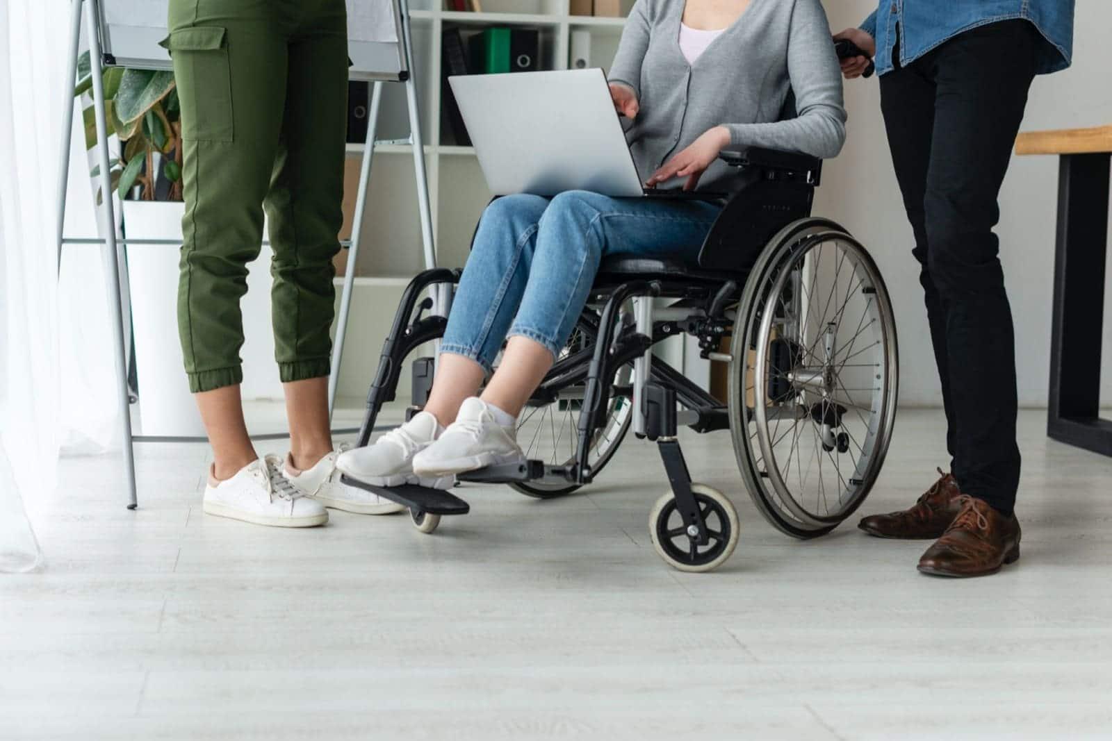 Varias personas trabajando silla de ruedas discapacidad